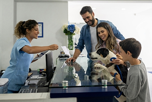 Happy family taking their dog to the vet